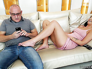 Mature white man on the couch with young and forlorn brunette